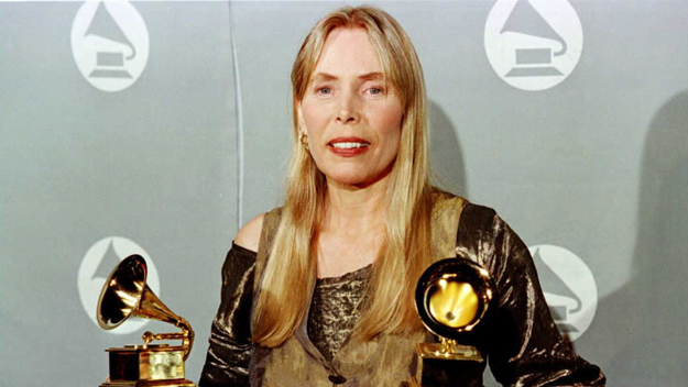 """Joni Mitchell smiles as she holds two Grammy Awards at 38th Annual Grammy Awards 28 February in Los Angeles. Mitchell won Grammys for Best Pop Album for """"Turbulent Indigo.""""   AFP PHOTO/Jeff Haynes (Photo by Jeff Haynes/Getty Images)"""